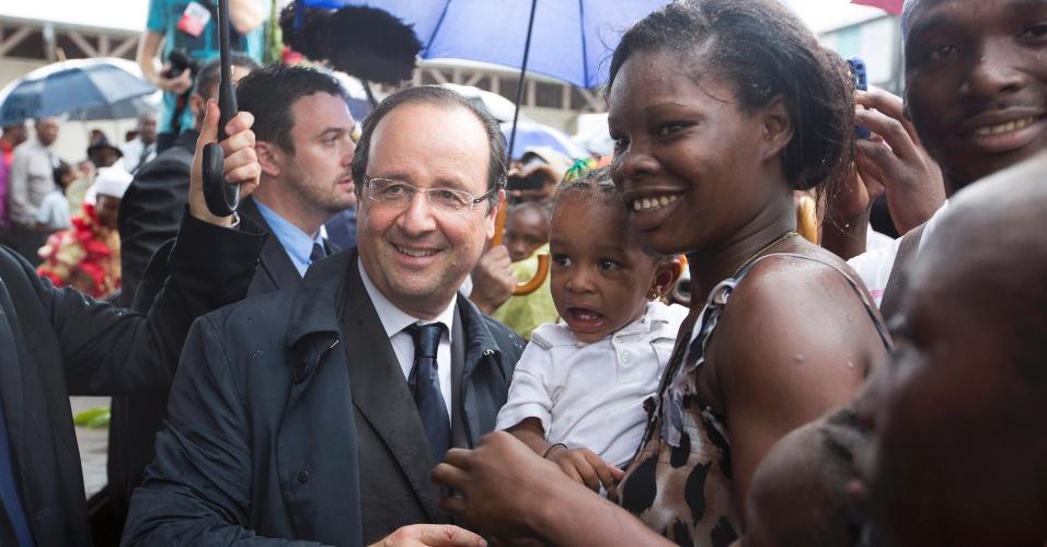 15.dez.2013 - François Hollande (e), presidente da França, posa com uma mulher segurando uma criança na cidade de Mana, durante o segundo dia de sua visita à Guiana, neste sábado (14)
