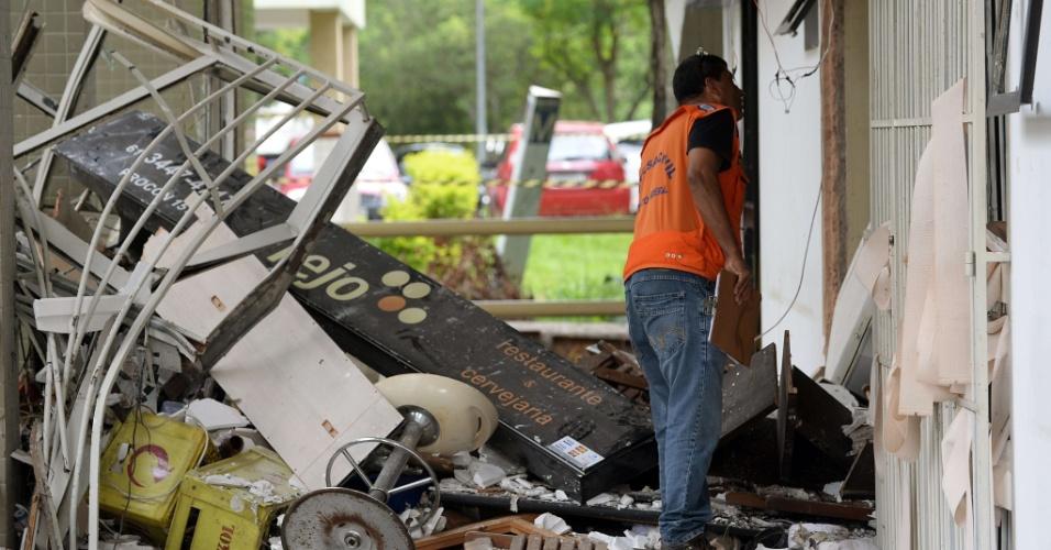 15.dez.2013 - Funcionário da Defesa Civil averigua estragos de explosão de gás próximo a um restaurante, que fica no térreo de um prédio em Brasília. Apesar da proporção do incidente, há apenas três pessoas feridas