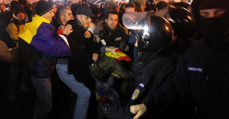 15.dez.2013 - Manifestantes entram em confronto com a polícia em frente ao palácio Victoria, sede do governo romeno, em Bucareste, capital do país. Centenas de romenos protestaram neste domingo depois que deputados aprovaram uma lei que aumenta a imunidade parlamentar daqueles acusados de corrupção