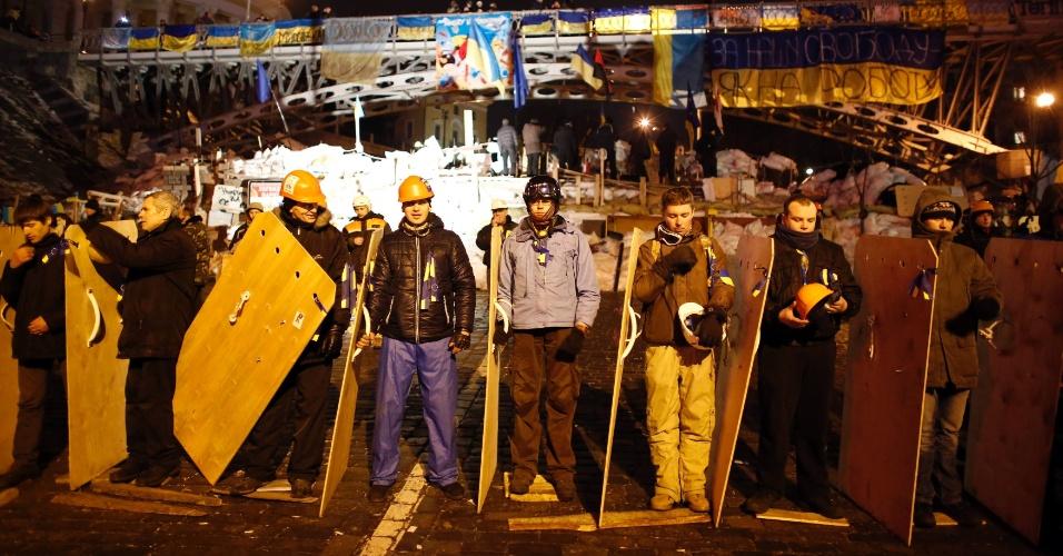 15.dez.2013 - Manifestantes ucranianos que apoiam um possível acordo com a UE (União Europeia) fazem linha de defesa contra a polícia na Praça da Independência, em Kiev