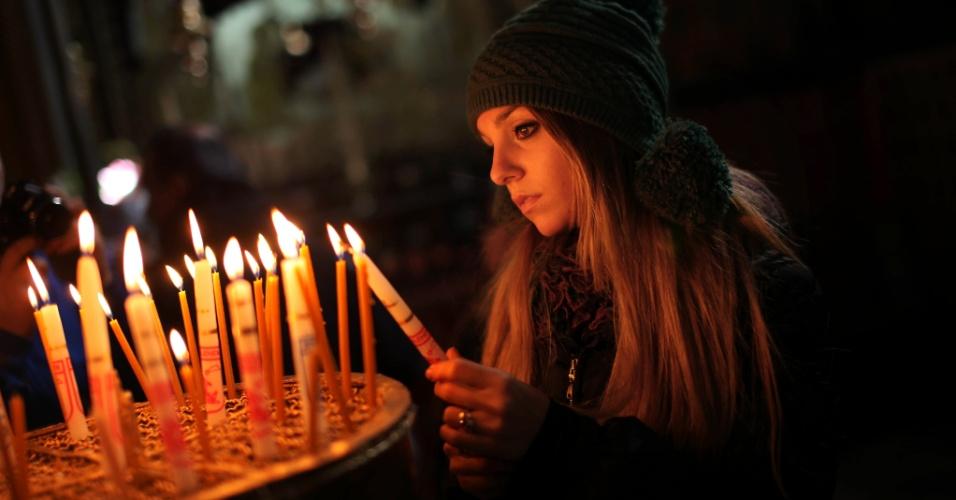 15.dez.2013 - Peregrina cristã acende vela no interior da Igreja da Natividade, na cidade de Belém, na Cisjordânia