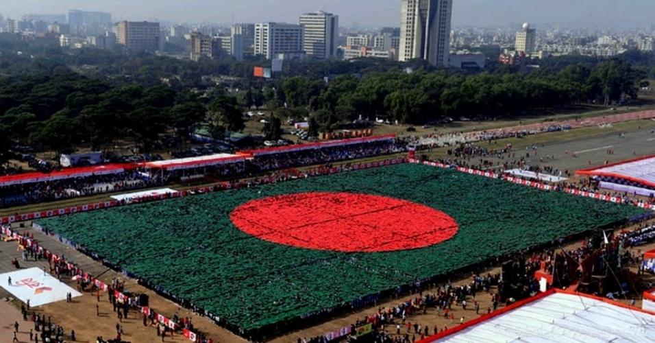 16.dez.2013 - Militares e estudantes de Bangladesh seguram cartazes para formar uma bandeira nacional, na capital Dacca, nesta segunda-feira (16). A participação de dezenas de milhares de voluntários permitiu que o grupo formasse a maior bandeira nacional do mundo, em uma tentativa de quebrar o recorde mundial do Guiness