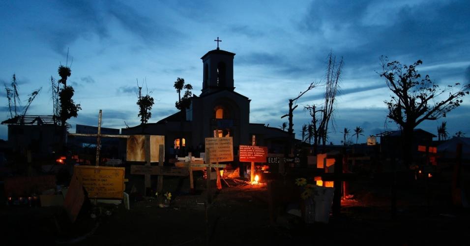16.dez.2013 - Valas comuns onde estão enterrados sobreviventes do tufão Haiyan, que devastou as Filipinas há um mês, ficam iluminadas por velas deixadas por familiares em frente à igreja onde acontece vigília de Natal em memória dos mortos, em Leyte.
