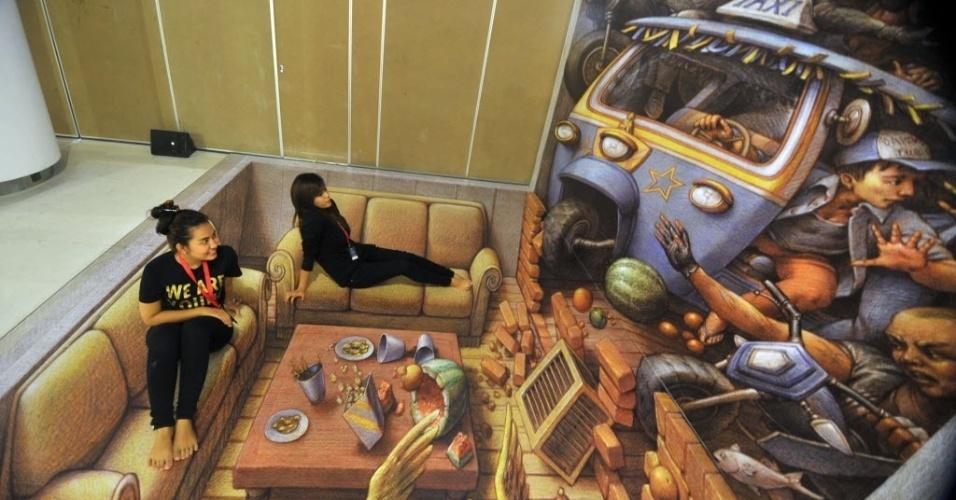 16.dez.2013 - Visitantes posam sobre pintura 3D criada pelo artista estadonidense Kurt Wenner, durante a exibição Artphoria 2013, no Centro Ciputra Artpenuer, em Jacarta, na Indosésia. As pinturas em 3D, aliadas às poses e encenações das pessoas, criam efeito de realidade em cenários de profundidade, dando sensação de altura e vertigem. A exposição Artphoria 2013 permanecerá no local até 26 de janeiro de 2014