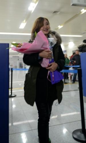 17.dez.2013 - Mulher ganha flores por ser a passageira de número 300.000 a chegar ao Aeroporto Internacional de Jinan na China. O areoporto chegou a este número nesta terça-feira (17)