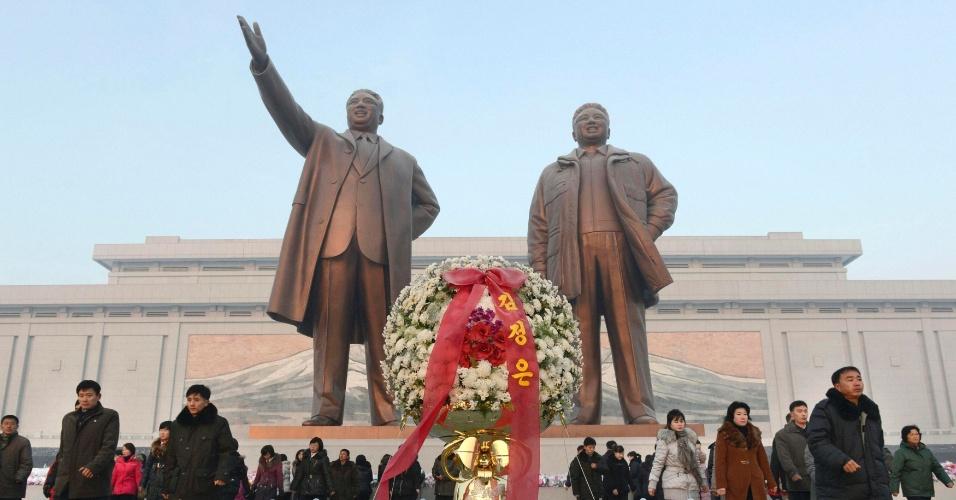 17.dez.2013 - Norte-coreanos depositam flores em estátuas de bronze dos líderes da Coreia do Norte (já falecidos), Kim Il Sung e  Kim Jong Il --respectivamente avô e pai do atual ditador, Kim Jon-un