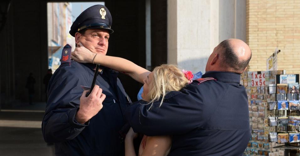 19.dez.2013 - A líder do grupo feminista Femen, Inna Shevchenko, tenta resistir à prisão durante protesto a favor do aborto realizado na praça de São Pedro, no Vaticano. A ativista escreveu no corpo