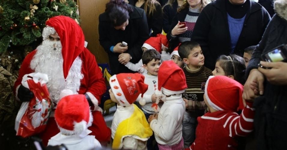 19.dez.2013 - Crianças sírias se reúnem com o Papai Noel em um jardim de infância em Damasco