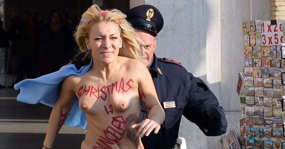 19.dez.2013 - Inna Shevchenko, líder do grupo feminista Femen, é perseguida por um policial fora praça de São Pedro, no Vaticano. Inna expôs os seios com a frase