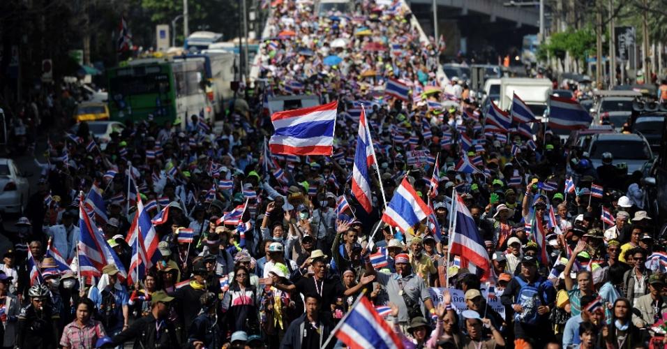 19.dez.2013 - Manifestantes antigoverno acenam bandeiras enquanto marcham pelas ruas de Bancoc (Tailândia) durante comício