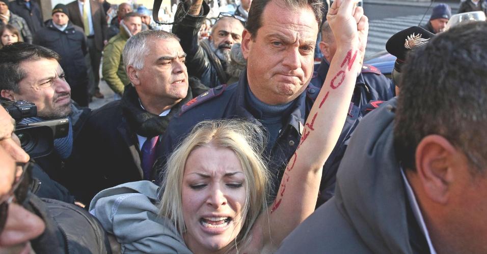 19.dez.2013 - Após cobrirem os seios da líder do grupo feminista Femen, Inna Shevchenko, policiais pretendem a ativista que protestava a favor do aborto na praça de São Pedro, no Vaticano