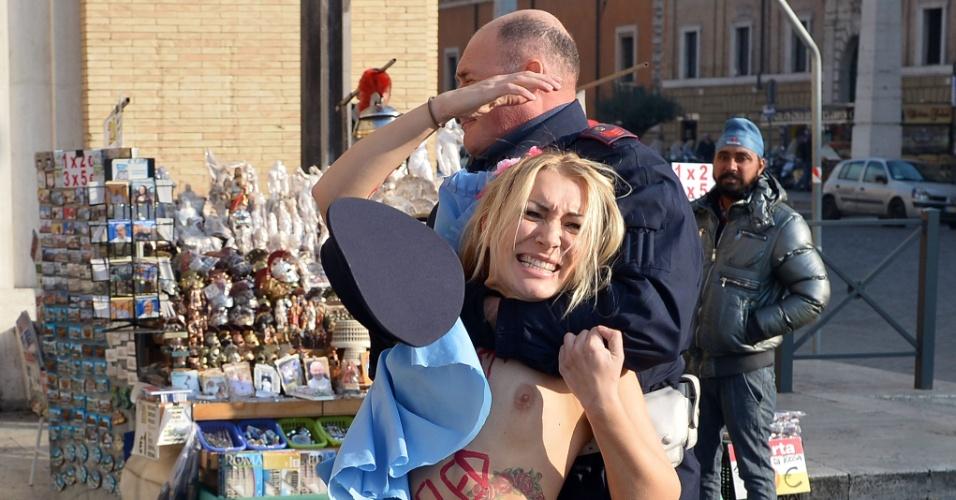 19.dez.2013 - Policial tenta deter a líder do grupo feminista Femen, Inna Shevchenko, durante protesto a favor do aborto realizado na praça de São Pedro, no Vaticano. Com os seis a mostra, a ativista escreveu no corpo