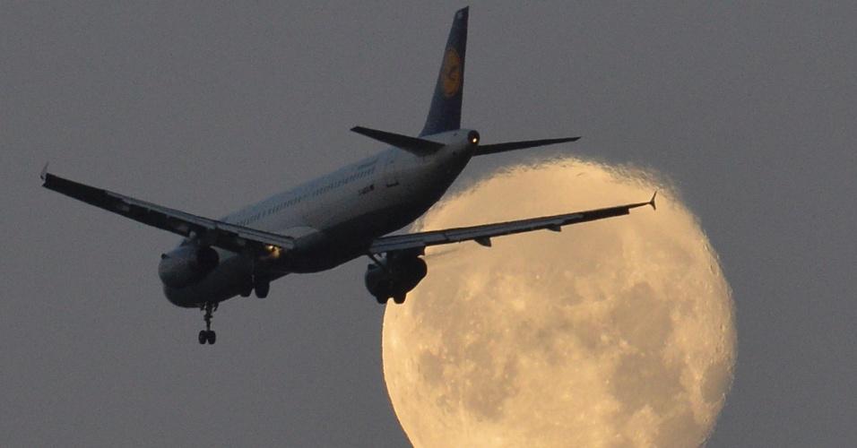 19.dez.2013 - Um avião passa pela lua cheia durante sua descida no aeroporto de Heathrow, em Londres, nesta quinta-feira (19). Grã-Bretanha vai considerar a construção de novas pistas nos terminais de Heathrow e Gatwick, em Londres