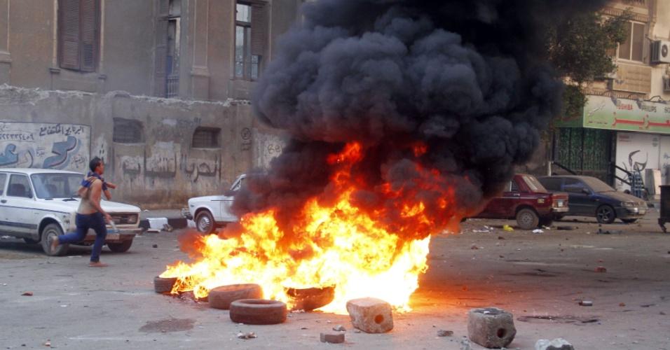 20.dez.2013 - Apoiadores da Irmandade Muçulmana corre do lado de pneus em chamas durante confrontos com policiais, no Cairo, nesta sexta-feira (20). Defensores do presidente deposto, Mohammed Mursi, realizam protestos quase diários e organizam manifestações maiores para as sextas-feiras, apesar da repressão que já matou mais de 1.000 pessoas em confrontos e prendeu milhares, mais desde a derrubada de Mursi pelos militares