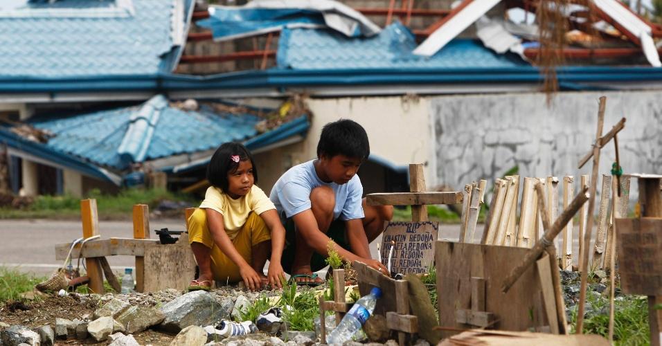 23.dez.2013 - Crianças acendem velas diante do túmulo de cinco irmãos, que morreram durante a passagem do supertufão Haiyan, em Tanuan, na região central das Filipinas