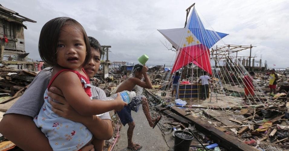 24.dez.2013 - Sobreviventes do tufão Haiyan, que devastou a região central das Filipinas, constroem uma lanterna em preparação para o Natal em Tacloban