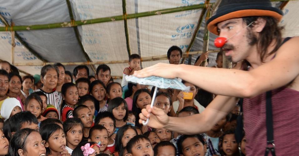 25.dez.2013 - Membro do grupo Palhaços Sem Fronteiras apresenta mágica para jovens sobreviventes do tufão Haiyan em Tacloban, nas Filipinas