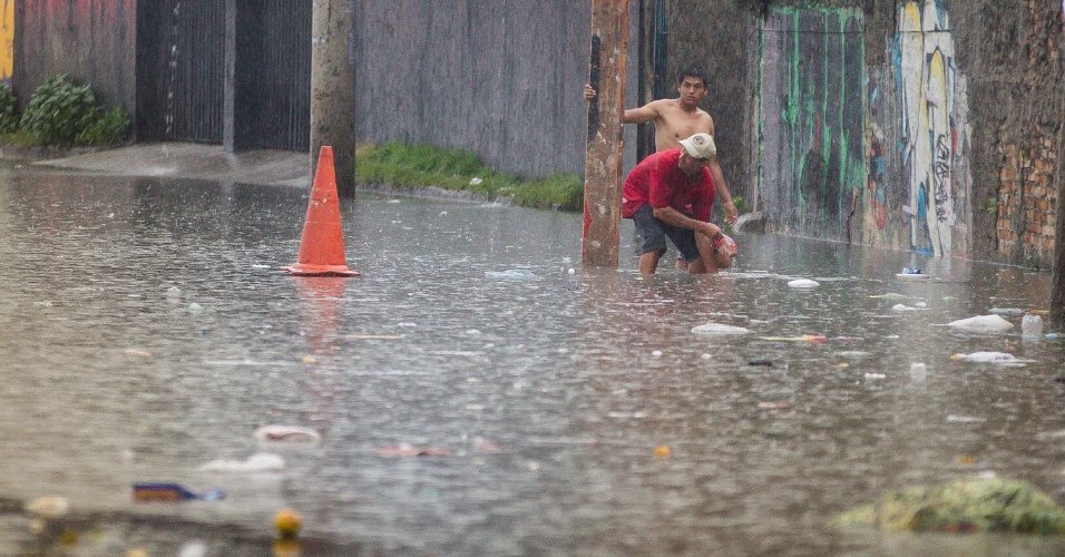 25.dez.2013 - Moradores tentam desentupir bueiros na avenida do Estado, em São Paulo, na pista sentido centro. A via chegou a ficar interditada em função do alagamento