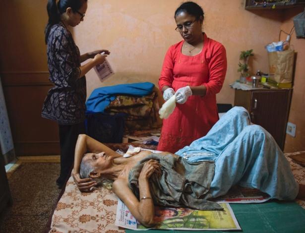 Enfermeiras cuidam de Sudershan Talwar, paciente com câncer de mama, em Nova Deli, na Índia
