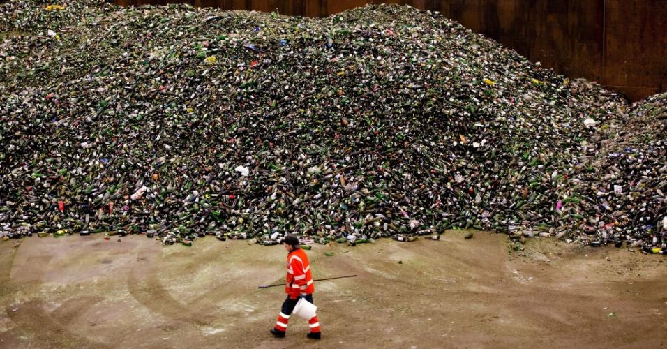2.jan.2014 - Homem caminha ao lado de uma enorme pilha de garrafas em um centro de reciclagem de vidro em Gameren, Holanda.  Caminhões não param de chegar transbordando de garrafas que ficaram acumuladas durante as férias