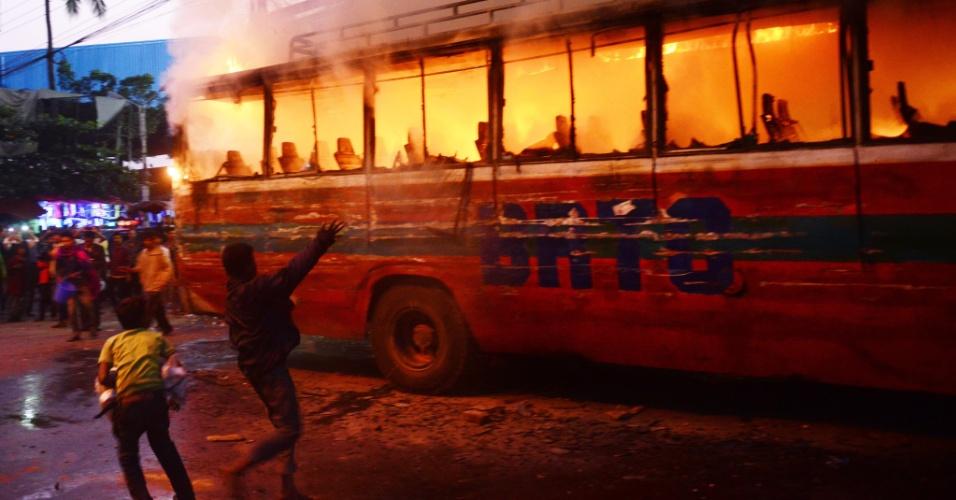 2.jan.2014 - Jovens tentam jogam areia em ônibus em chamas para tentar apagar o fogo, em Dacca, Bangladesh. O ônibus foi incendiado por manifestantes que opõem as próximas eleições. O principal partido de oposição convocou protestos contra as eleições no país