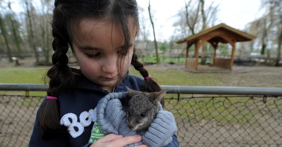 """2.jan.2014 - Lina Ismer, 6, filha de Julia Ismer, diretora do zoológico Tierpark Stroehen, segura o bebê canguru """"Karl Friedelich"""" em um gorro de lã em Stroehen, noroeste da Alemanha. Depois que mãe do canguru morreu, ele foi adotado pela diretora do parque"""