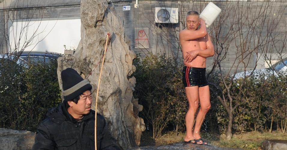 2.jan.2014 - Um nadador se lava após seu mergulho diário em lago congelado em Pequim, na China, nesta quinta-feira (2). Os lagos de Pequim atraem dezenas de turistas e moradores locais que costumam patinar no gelo ou nadar
