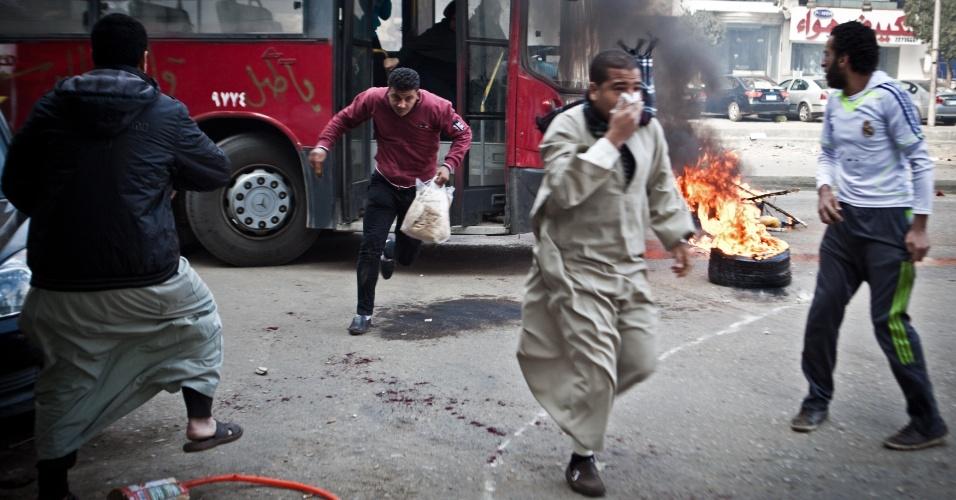 3.jan.2014 - Homens correm para for a de um ônibus público depois de ele ser tomado durante confrontos entre apoiadores do ex-presidente egípcio deposto, Mohammed Mursi, e policiais no nordeste do Cairo, na cidade de Nasr, nesta sexta-feira (3). Treze pessoas morreram durante os conflitos desta sexta, segundo informações de agências internacionais de notícias