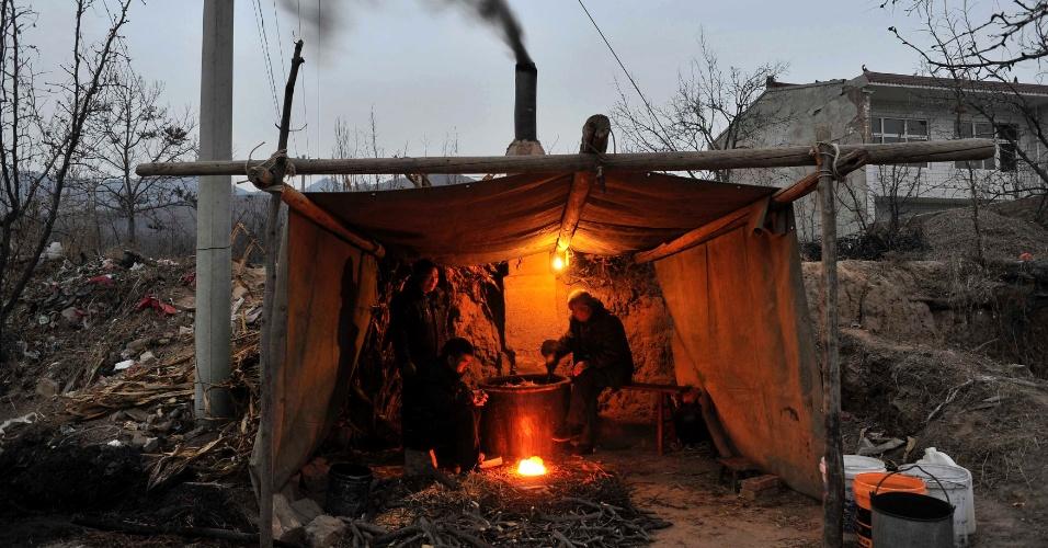 6.jan.2014 - Moradores de Ruicheng, centro-leste da China, produzem vinho de caqui, bebida tradicional local, dentro de tenda improvisada, em imagem deste domingo (5)