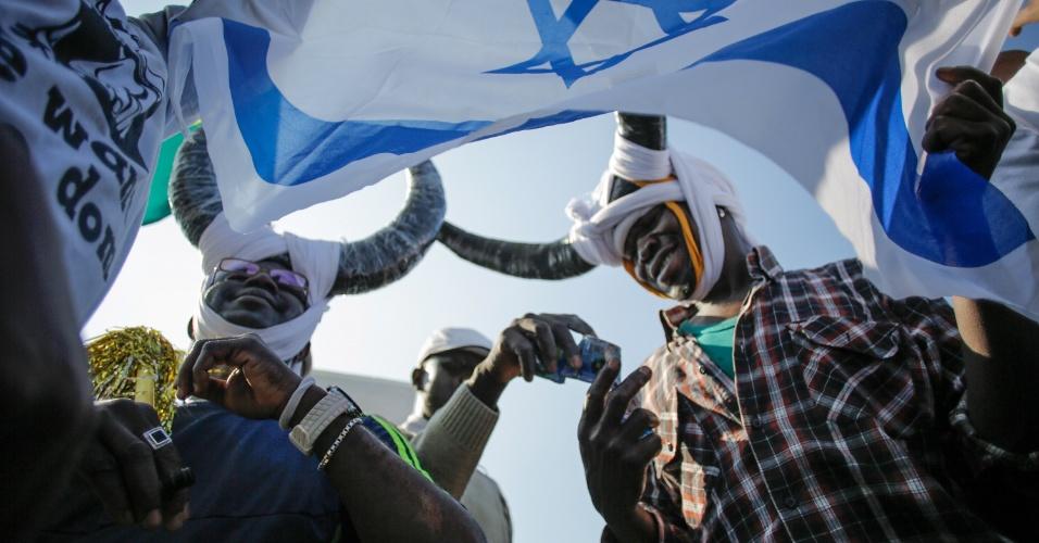 6.jan.2014 - Africanos que querem asilo em Israel agitam a bandeira israelense durante protesto em frente à embaixada dos Estados Unidos pedindo abrigo e direitos trabalhistas do governo em Tel Aviv, nesta segunda-feira (6), no segundo dia de protestos massivos contra as políticas de imigração israelenses