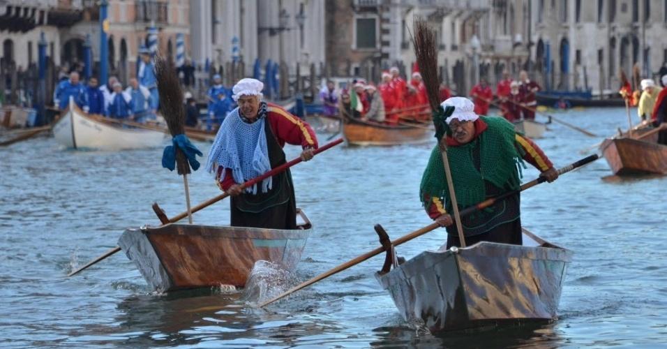 """6.jan.2014 - Gianni Colombo (à direita) e Giovanni Rossi (esquerda), vestidos com trajes tradicionais competem na regata ?""""Befana"""" no Grande Canal de Veneza, Itália. Colombo venceu a corrida que é realizada para marcar o Dia de Reis"""