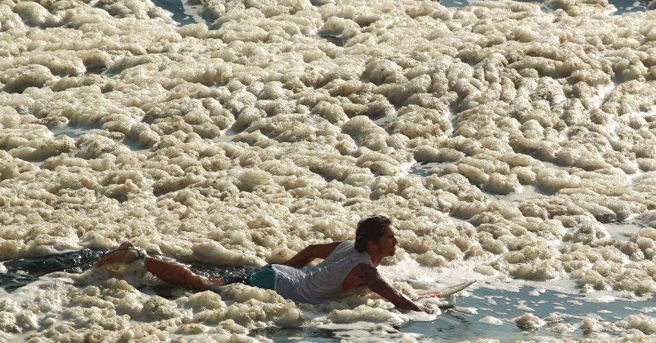 6.jan.2014 - Homem ignora espuma na praia do Leblon, Rio de Janeiro, e tenta surfar. Segundo especialistas, a mudança na coloração da água e a formação de espuma nesta época do ano estão geralmente associadas à floração e à decomposição de fitoplânctons (algas)