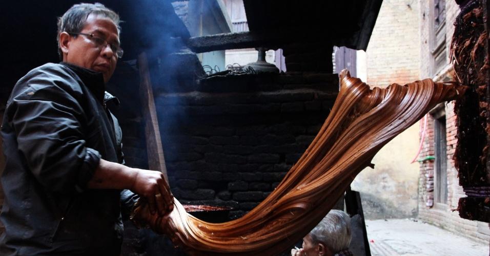 6.jan.2014 - Um homem prepara um melaço (chaku, no idioma local) para o Festival Maghe Sankranti, em Lalitpur, Nepal, nesta segunda-feira (6). O melaço que se produz e é consumido geralmente durante o festival e todo o inverno pelos nepaleses, é preparado basicamente caldo de cana de açúcar concentrado, açúcar mascavo, nozes e outros ingredientes