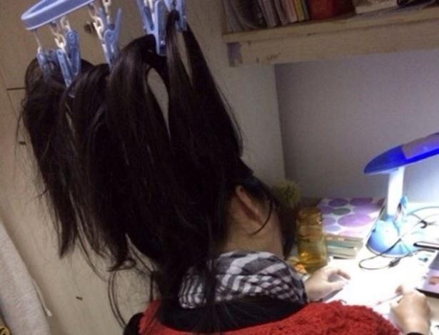 Estudante chinesa prende os cabelos para o alto para evitar o cochilo durante as noites de estudo