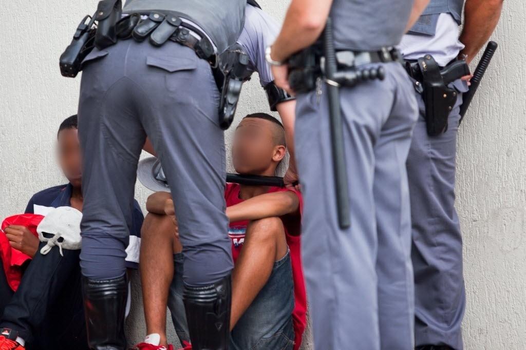 11.jan.2014 - Policial militar usa cassetete para intimidar jovem durante
