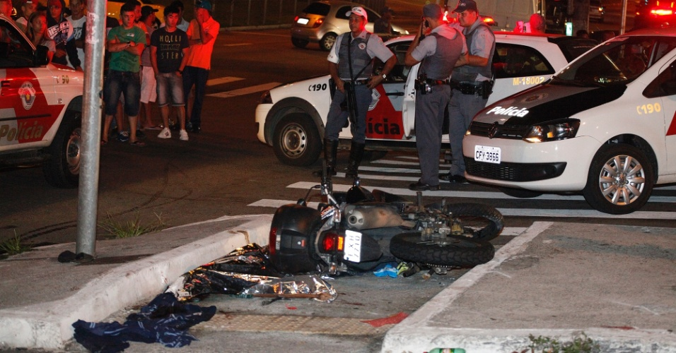14.jan.2014 - Curiosos e policiais observam local onde um policial militar reagiu a assalto, na Freguesia do Ó, zona norte de São Paulo, e baleou dois bandidos, na madrugada desta terça-feira (14). Um dos assaltantes morreu no local; o outro foi socorrido e levado a um pronto-socorro da região