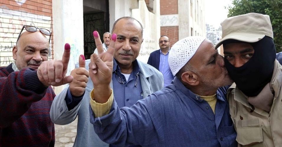 15.jan.2014 - Homem egípcio beija um membro da força de segurança do Egito, enquanto mostra o dedo manchado de tinta, ao lado de outros eleitores. Os colégios eleitorais voltaram a abrir nesta quarta-feira para o segundo e último dia de votação sobre a nova Constituição do país