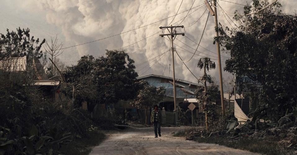 15.jan.2014 - Morador de uma vila próxima ao vulcão Sinabung caminha se protegendo das cinzas. De acordo com a mídia local, a erupção já causou a retirada de 25 mil moradores de áreas de risco e fez com que o governo da Indonésia aumentasse o alerta de perigo para o seu nível mais alto desde novembro de 2013