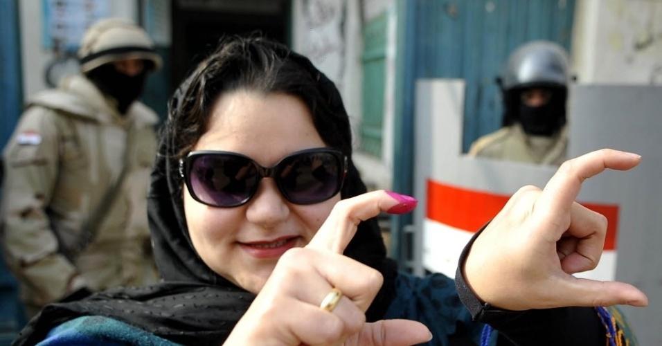 15.jan.2014 - Mulher egípcia faz gesto que indica apoio ao ministro da Defesa, chefe do Exército do Egito, Abdel Fattah al-Sisi, depois de votar sobre a nova Constituição do país