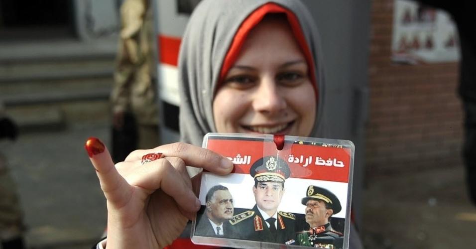 15.jan.2014 - Mulher egípcia mostra o dedo manchado de tinta enquanto segura um cartão com retratos dos presidentes do Egito Gamal Abdel Nasser (esquerda) e Anwar Sadat (direita) ao lado de ministro da Defesa, chefe do Exército do país, Abdel Fattah al-Sisi (centro), o texto em árabe diz:
