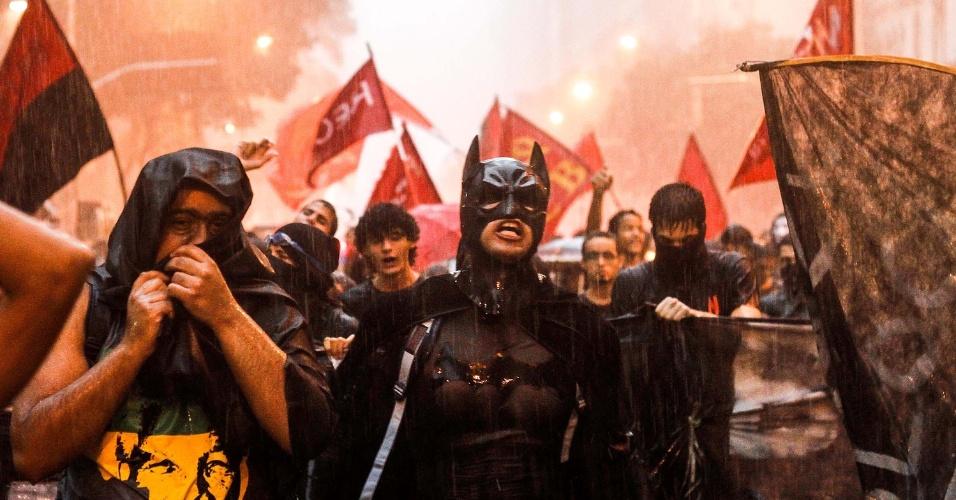 16.jan.2014 - Figura conhecida dos protestos no Rio de Janeiro, Batman participa de manifestação contra o aumento das passagens do transporte público na capital fluminense, no centro do Rio, nesta quinta-feira (16), embaixo de forte chuva. Os manifestantes se reuniram na praça localizada atrás da Igreja da Candelária, acompanhados por dezenas de policiais militares