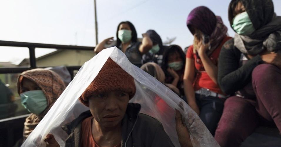 16.jan.2014 - Moradores de vilarejo na Indonésia usam pedaços de plástico para se proteger das cinzas do vulcão Monte Sinabung. Mais de 25 mil pessoas precisaram ser evacuadas desde que as autoridades emitiram alerta máximo por causa do vulcão, em novembro de 2013