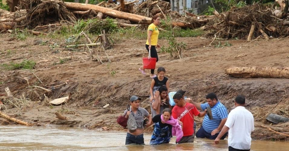 16.jan.2014 - Moradores ribeirinhos atravessam o rio Palmital. A cidade de Itaoca (347 km de SP), no extremo sul do Estado, está em situação de emergência em virtude das fortes chuvas que atingiram a região nos últimos dias