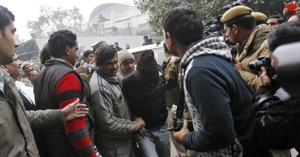 16.jan.2014 - Policiais à paisana escoltam suspeito de participar do estupro coletivo de uma turista dinamarquesa em Nova Déli, na Índia. De acordo com a mídia local, a polícia indiana prendeu dois suspeitos de participar do crime nesta quinta-feira (16)
