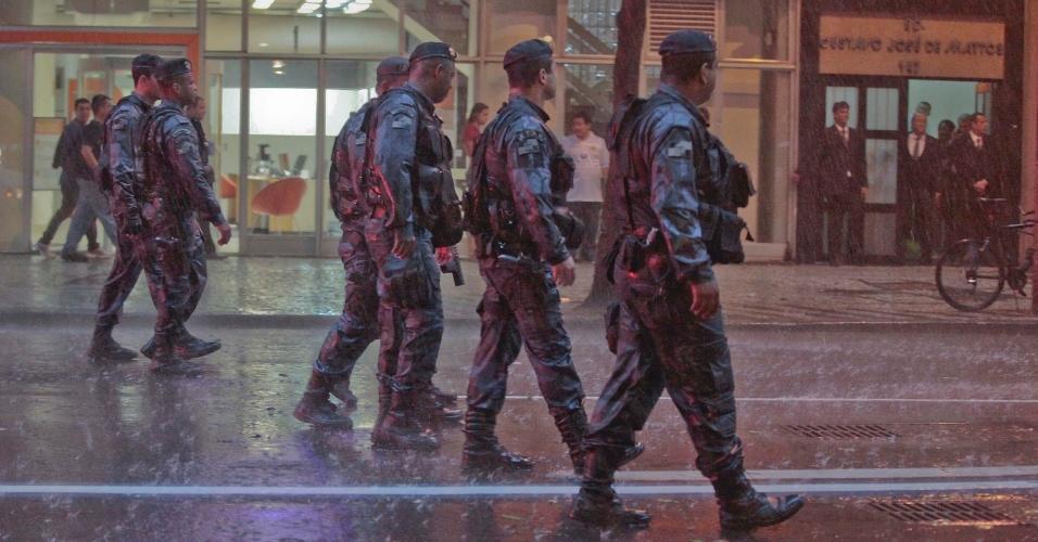 16.jan.2014 - Sob forte chuva, policiais acompanham protesto contra o aumento das passagens do transporte público na capital fluminense, nesta quinta-feira (16), no centro do Rio de Janeiro