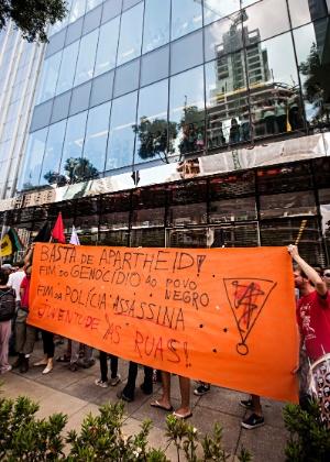 18.jan.2014 - Manifestantes erguem faixa durante protesto contra racismo e discriminação em frente ao Shopping JK Iguatemi, no Itaim Bibi, na zona oeste de São Paulo, neste sábado (18), motivados por conta da onda dos chamados rolezinhos. O centro de compras fechou as portas durante o protesto. Segundo a administração do shopping, ele será reaberto apenas no domingo (19)
