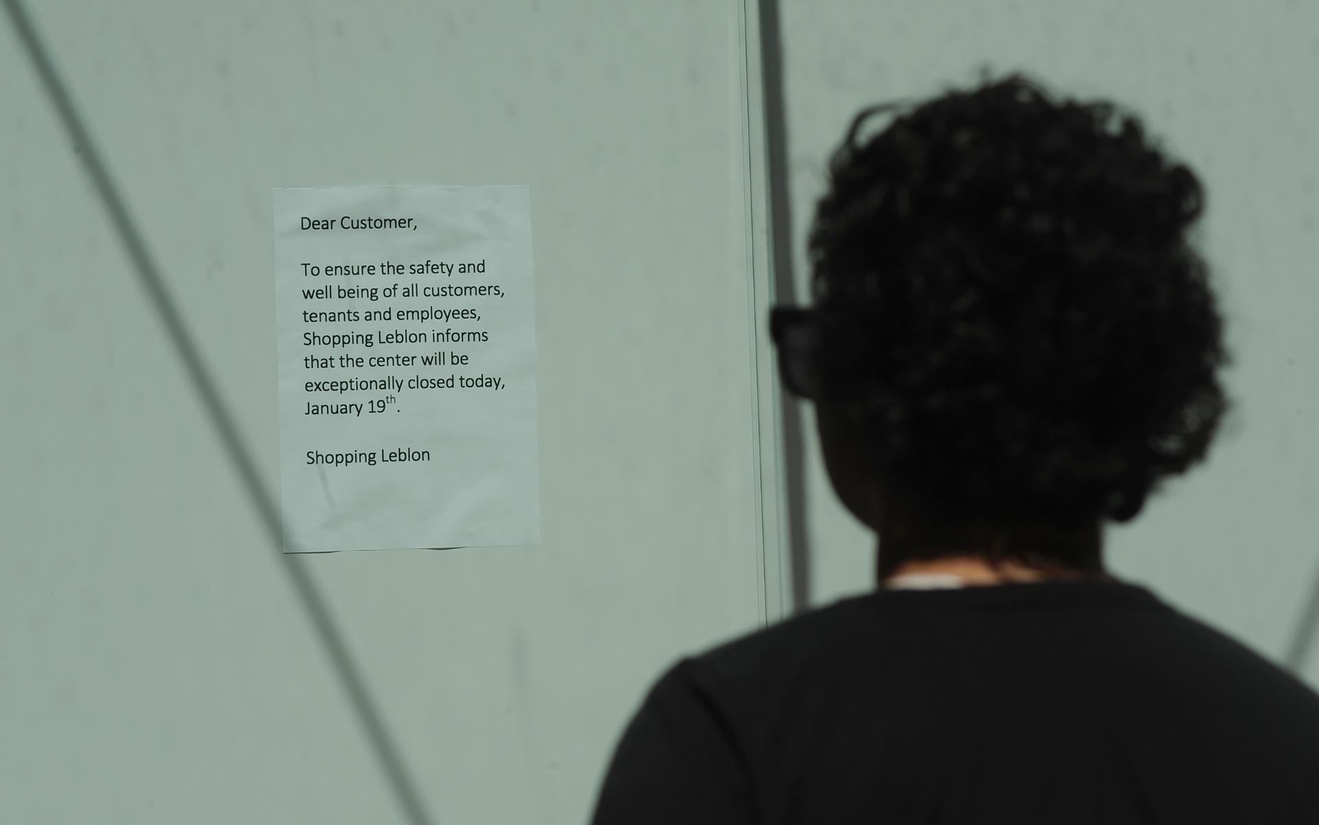 19.jan.2014 - Pessoa lê comunicado preso à fachada do shopping Leblon, na zona sul do Rio de Janeiro, informando que o centro comercial ficará fechado neste domingo (19) para a segurança dos clientes e funcionários. No local, foi marcado um