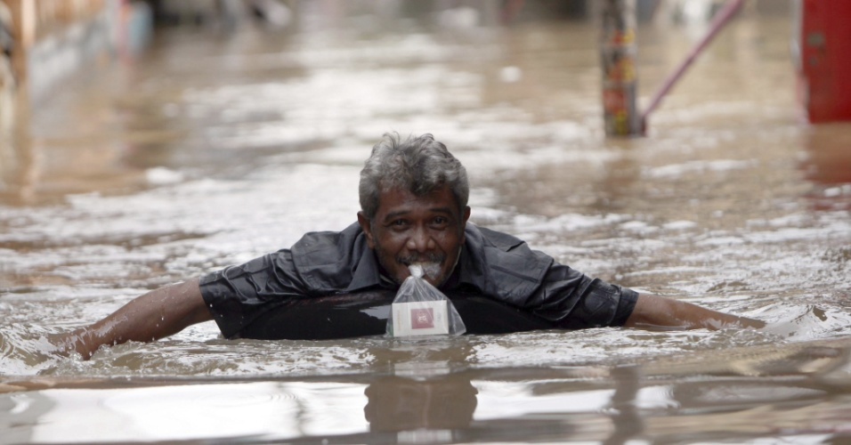 20.jan.2014 - Homem tem agua no pescoço em rua completamente inundada em Jacarta, na Indonésia, nesta segunda-feira (20). As grandes inundações atingiram a capital do país deixaram ao menos dez mortos e 64 mil desalojados