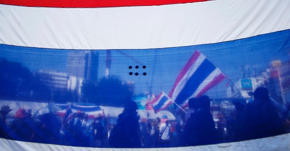 """20.jan.2014 - Manifestantes antigoverno na Tailândia são fotografados por trás de uma bandeira do país enquanto eles marchavam em direção a um banco estatal na capital, Bancoc. A mídia local informou que o governo tailandês está """"muito seriamente"""" considerando a possibilidade de decretar estado de emergência após mais um fim de semana de violentos protestos contra as a primeira-ministra Yingluck Shinawatra"""
