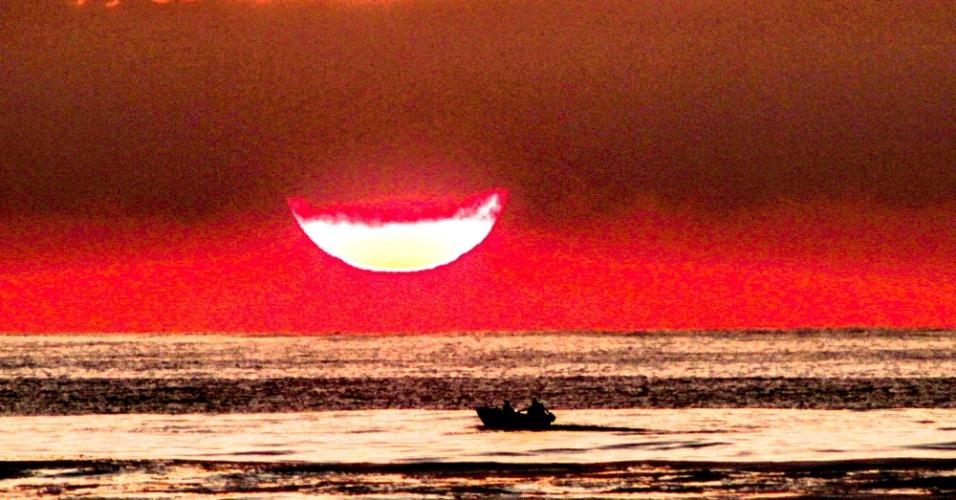 20.jan.2014 - O feriado de São Sebastião, no Rio de Janeiro, começou com sol forte e calor intenso nesta segunda-feira. Na praia do Recreio dos Bandeirantes, o pescador cruza o mar com o sol nascente no horizonte